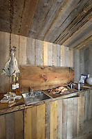 A rudimentary kitchen along one wall of the living room cabin is concealed beneath a lid of recycled wood