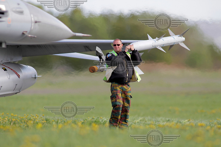 Crew member hold on to a missile as a Belgian F-16 is guided to parking. Nato Tiger Meet is an annual gathering of squadrons using the tiger as their mascot. While originally mostly a social event it is now a full military exercise. Tiger Meet 2012 was held at the Norwegian air base Ørlandet.