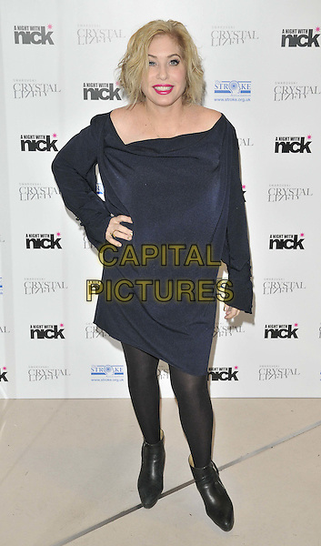 """Brix Smith-Start.The """"A Night With Nick"""" charity event in aid of The Stroke Association, Swarovski CRYSTALLIZED, Gt. Marlborough St., London, England..December 6th, 2011.full length black dress blue velvet pink lipstick boots tights hand on hip.CAP/CAN.©Can Nguyen/Capital Pictures."""