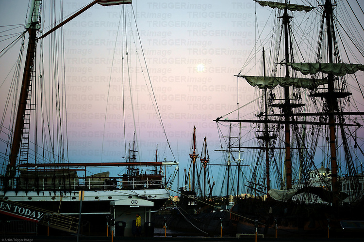Old sailing ships of the Maritime Museum of San Diego are in the sunrise in the port of San Diego.