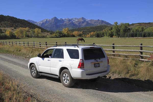White SUV on dirt road in the Sneffels Range near Telluride, Colorado, USA.