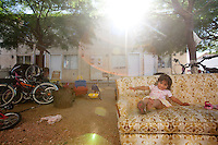 leaving0627 Alondra Rosario, 21 months, sits on a couch outside her family's West Valley apartment. Her family traveled with the Sanchez family to start a new life in Pennsylvania. She is a U.S. citizen but her parents are both in the country illegally. (Pat Shannahan/ The Arizona Republic)