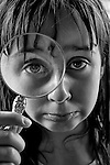 Young girl with a magnifyng glass and funny expression on face