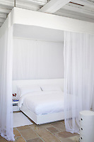 A spacious white bedroom with a double bed enclosed by a sheer curtain with bed canopy.