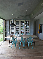 The kitchen/dining area is furnished with a scrubbed wood table flanked by a set of painted bistro chairs