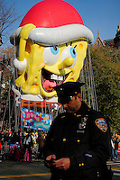 The SpongeBob SquarePants balloon floats through the parade route while A New York Police officers checks his mobile phone during the 89th Macy's Thanksgiving Annual Day Parade in the Manhattan borough of New York.  11/26/2015. Eduardo MunozAlvarez/VIEWpress