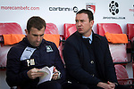 Visiting manager Derek Adams (right) and first team coach Paul Wotton taking their seats at the Globe Arena before Morecambe hosted Plymouth Argyle in a League 2 fixture. The stadium was opened in 2010 and replaced Morecambe's traditional home of Christie Park which had been their home since 1921, the year after their foundation. Plymouth won this fixture by 2-0 watched by 2,081 spectators, in a game delayed by 30 minutes due to traffic congestion affecting travelling Argyle fans.