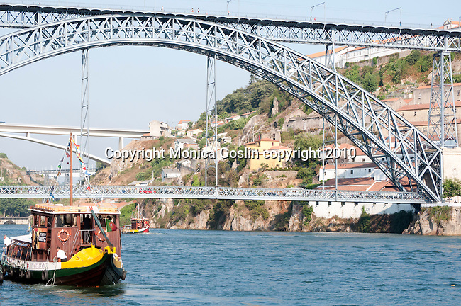 Colorful boats cruise down the Douro River in Porto, Portugal with three bridges visible in the background, the closest one being the Don Luis iron bridge.