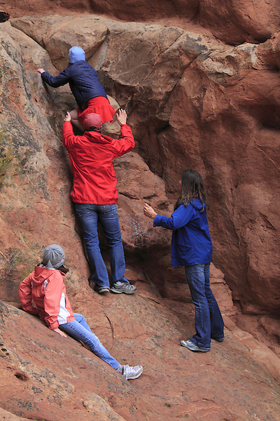 Mom and dad helping daughters to  climb a rock wall in Arches National Park, Moab, Utah, USA. .  John offers private photo tours in Arches National Park and throughout Utah and Colorado. Year-round.