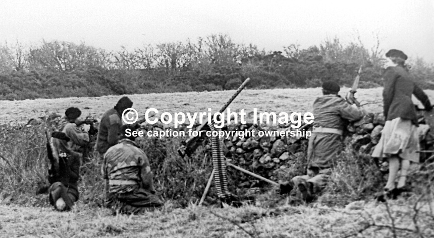 This republican movement press release photograph claims to be of a Provisional IRA border unit on manoeuvres in Co Fermanagh, N Ireland, February 1977.  The men and women volunteers are seen using a variety of weapons i.e. a 50 mm Browning M2 machine gun, a 30 mm machine gun and other automatic weapons. 197702130024e<br />