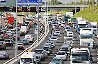 Traffic congestion cars and trucks travelling in both directions on M25 motorway, London, United Kingdom