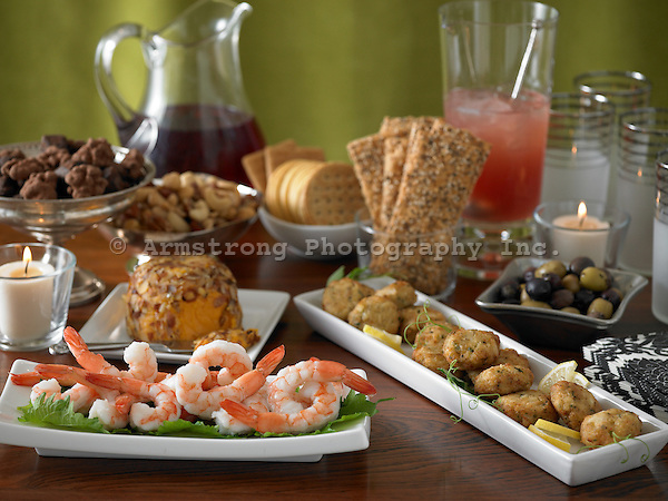 A table with appetizers for a fall celebration/Thanksgiving. Includes shrimp, olives, beverages, cheese, nuts, crackers, and chocolates.