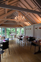Tables laid for lunch in the conservatory style dining room of Whitehouse, a guest house in Chillington, Devon