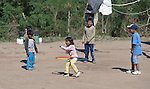 Other children watch as Soli Marita, a 3-year old Wichi indigenous girl, performs with a hula hoop in Lote 75, an indigenous neighborhood of Embarcacion, Argentina. The Wichi in this area, largely traditional hunters and gatherers, have struggled for decades to recover land that has been systematically stolen from them by cattleraisers and large agricultural plantations.