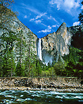 """Bridalveil Fall, 617 ft (188m), seasonal flows year round. Merced River in foreground. Ahwahneechee Native Americans called this waterfall Pohono, """"Spirit of the Puffing Wind"""". Yosemite National Park (est. 1906), 761,268 acres (3,080.74 km2), 1,189 sq mi (3,080 km2). Park elevations range from 2,127 to 13,114 feet (648 to 3,997 m) and contains five major vegetation zones: chaparral/oak woodland, lower montane, upper montane, subalpine, and alpine. Yosemite Valley carved by glacial movement about 1 million years ago. World Heritage Site (1984). Mariposa County, CA."""