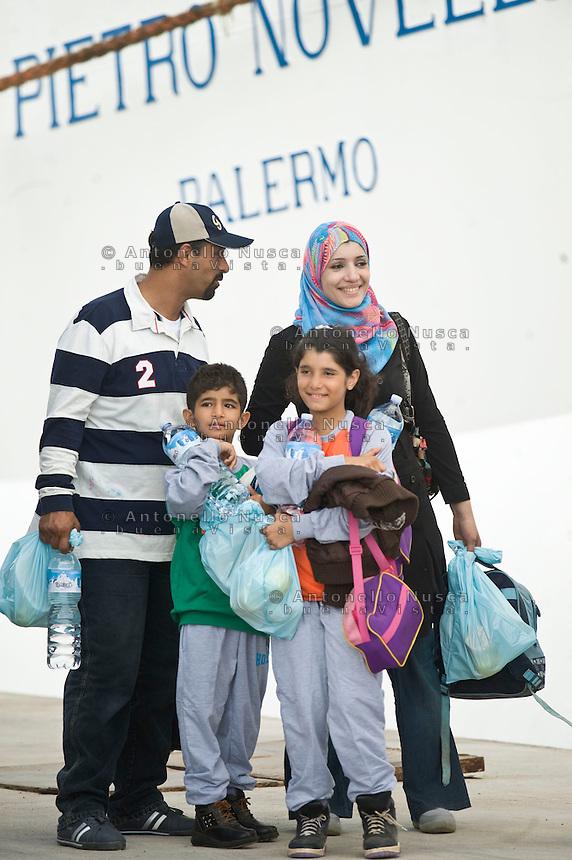 Profughi siriani lasciano l'isola di Lampedusa per raggiungere i centri di accoglienza in Sicilia.<br /> Immigrants wait to board a ship bound for Porto Empedocle, Sicily on October 4, 2013 in Lampedusa, Italy.