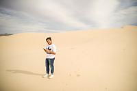 A man obcervates his cell phone, smartphone in the sand dunes of the Samalayuca Desert, Chihuahua Mexico. 52 km south of Ciudad Juárez in the middle of the desert area known as the Médanos de Samalayuca. This tourist and travel destination belongs to the Municipality of Ciudad Juárez in northern Mexico.<br /> (Photo: Luis Gutierrez / NortePhoto)<br /> <br /> un hombre obcerva su celular, smartphone en las dunas de arena del desierto de Samalayuca, Chihuahua Mexico. A 52 km al sur de Ciudad Juárez en medio de la zona desértica conocida como los Médanos de Samalayuca. Este destino turístico y de viajes pertenece al Municipio de Ciudad Juárez en el norte de Mexico. <br /> (Foto: LuisGutierrez/NortePhoto)