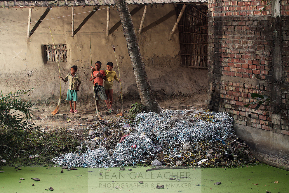Three boys stand near e-waste discarded at the side of a small pond in Sangrampur. As electronic waste is broken down, harmful elements such as mercury, lead and arsenic leach into the soil and water, resulting in the long-term poisoning of local resources. India. November, 2013