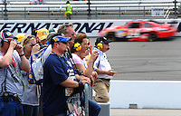 May 1, 2009; Richmond, VA, USA; Fans look on as NASCAR Sprint Cup Series driver Tony Stewart races by in the background during practice for the Russ Friedman 400 at the Richmond International Raceway. Mandatory Credit: Mark J. Rebilas-
