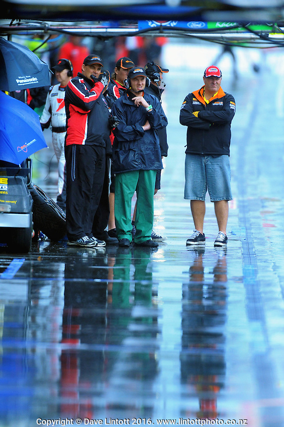 Pit crews watch the racing in the rain. V8 Supercars - ITM 400 day two at Hamilton Street Circuit, Hamilton, New Zealand on Saturday, 16 April 2011. Photo: Dave Lintott / lintottphoto.co.nz