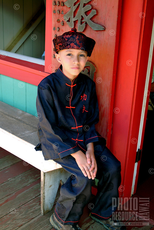 A young boy dressed in traditional attire outside the Chinese temple at Hawaii Plantation Village.