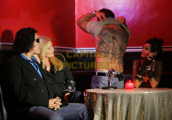"GENE SIMMONS, SHANNON TWEED & TODD NEWMAN.Dave Navarro's live weekly internet show ,"" Spread Entertainment "" on Maniatv.com held at The Dragonfly in Hollywood, California, USA..August 23rd, 2007.half length black top jacket couple sunglasses shades sitting lifting shirt tattoo back behind rear .CAP/DVS.©Debbie VanStory/Capital Pictures"