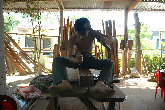 A Vietnamese carpenter works in his home in Hoi An, Vietnam.