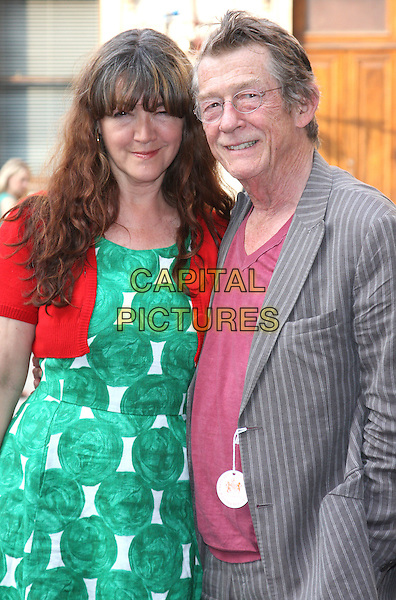 Anwen Rees Meyers &amp; John Hurt<br /> Royal Academy Summer Exhibition VIP Private View at the Royal Academy, Piccadilly, London, England.<br /> June 2nd 2011<br /> half length green print dress red cardigan grey gray pinstripe suit married husband wife <br /> CAP/ROS<br /> &copy;Steve Ross/Capital Pictures