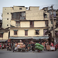 Workers transport goods around Han Zheng Street in Wuhan, Hubei province, December 2011. Han Zheng Street is central China's largest wholesale distribution centre for clothing, electrical appliances, household goods, etc. (Mamiya 6, 75mm f3.5, Kodak Ektar 100 film)