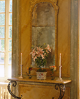 A faded antique gilt-framed mirror hangs above a marble-topped console table in this dining room