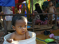 Koh Lanta, Thailand--Ten-month old Suwaimee Ninthong bathes in a bucket in front of the tent he shares with his family after their home was destroyed by the Tsunami in the village of Hua Laem on Koh Lanta island, Thailand.  In the background, his mother, Korntip, tries to coax her daughter, Gitnmaree (2) to put on her clothes after her bath.  The family also lost Korntip's father who was trying to save his fishing boat when the second wave came.  The family has yet to find his body and is unable to proceed with funeral services without it.  01/21/05 © Julia Cumes / The Image Works