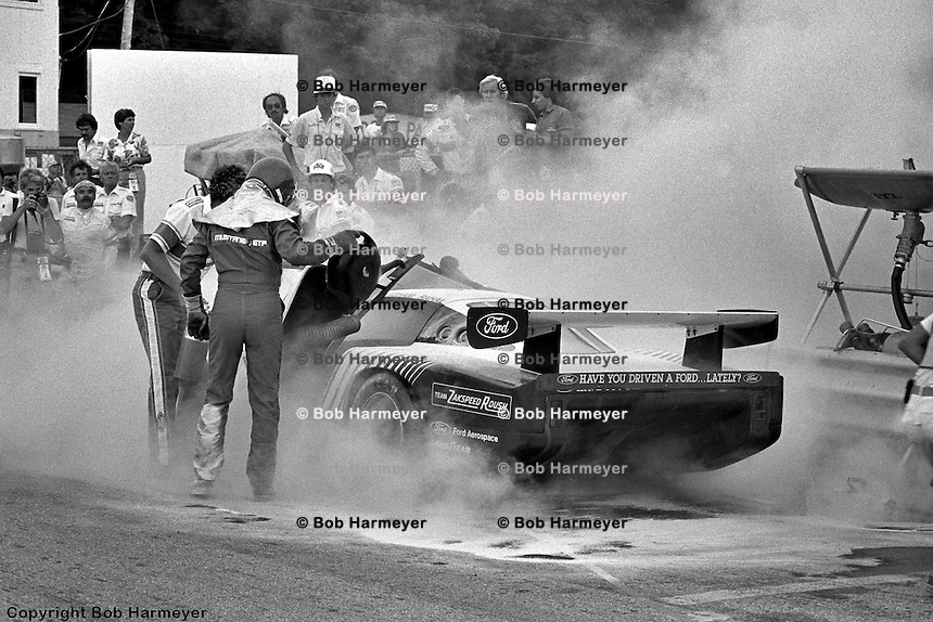 Bobby Rahal (center, in helmet and driving suit) helps co-driver Geoff Brabham from their Ford Mustang GTP car after fire broke out during a pit stop during the 1983 IMSA race at Road America near Elkhart Lake, Wisconsin.