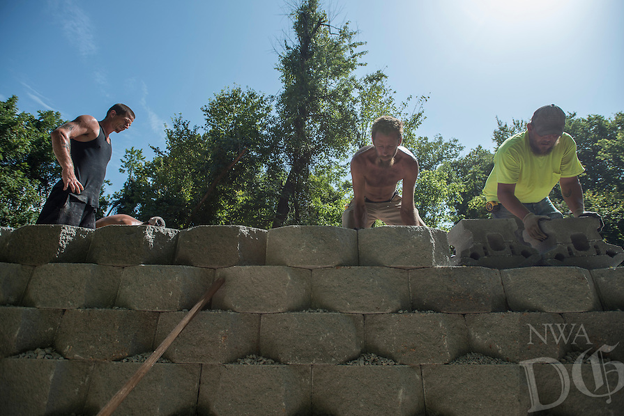 STAFF PHOTO ANTHONY REYES &bull; @NWATONYR<br /> Shay Mayes, center, and Marty Graham, right, set stones, as Jason Leftwich, all with Mayes Masonry, takes a breather, as they build a decorative retaining wall Wednesday Aug. 20, 2014 near Lake Springdale. The wall will support part of the Razorback Greenway trail connection to the Lake Springdale trail. Each block weighs 90 pounds and a crew has built 420 feet of retaining wall reaching as much as seven feet tall in places.