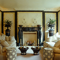 The black faux marble mantelpiece is flanked by a pair of iron urns on pedestals in this well-furnished sitting room