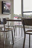 Shiny silver chairs are set around the dining table which seats 10 and is made of a bleach wood with bespoke aluminium legs.