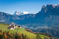 Italy, Alto Adige - Trentino (South Tyrol), Renon: view across village Monte di Mezzo with church St. Nikolaus (built 1200) towards the Dolomites with Sassolungo (Langkofel), Sasso Piatto (Plattkofel) and Sciliar (Schlern) mountains   Italien, Suedtirol (Alto Adige-Trentino), Ritten: Blick ueber Mittelberg am Ritten mit der St. Nikolauskirche (erbaut um 1200) in die Dolomiten mit Langkofel, Plattkofel und dem Schlern (rechts)