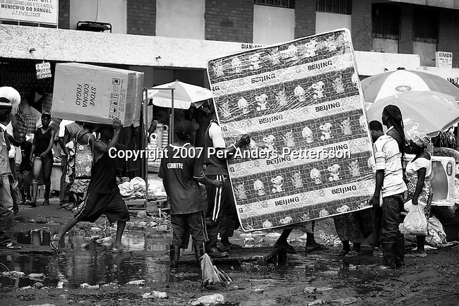 """LUANDA, ANGOLA MARCH 31: Angolan workers carry a mattress with """"Beijing 2008"""" written on it on March 31, 2007 at the Chinese market in Luanda. Luanda is full of newly arrived Chinese who do business in many different fields. Tens of thousands of Chinese has come to Africa the last years to work in infrastructure projects and businesses. Chinese companies are often the lowest bidders for contracts, pricing out the more expensive European companies. The Chinese people often live where they work and rarely interact with the local population. Most Chinese don't speak English and they are mostly staying in the compounds cooking their Chinese food. (Photo by Per-Anders Pettersson).."""