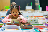 NWA Democrat-Gazette/JASON IVESTER<br /> Jillian Matlock, first-grader, looks over books Thursday, May 4, 2017, at Vandergriff Elementary School in Fayetteville. The book sale continues today (FRIDAY) with proceeds going to benefit the Fayetteville Animal Services.