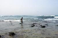 Senegal. Dakar. Virage beach. Man walks to the atlantic ocean to swim. © 2000 Didier Ruef