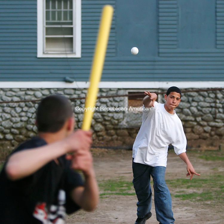 WATERBURY, CT 4/22/07- 042207BZ03- Angel Narvaez, 16, of Waterbury, pitches to Anthony Colon, 15, of Waterbury, during a game of Wiffle Ball in a lot on the corner of Cooke Street and Pine Street in Waterbury Sunday afternoon. <br /> Jamison C. Bazinet Republican-American