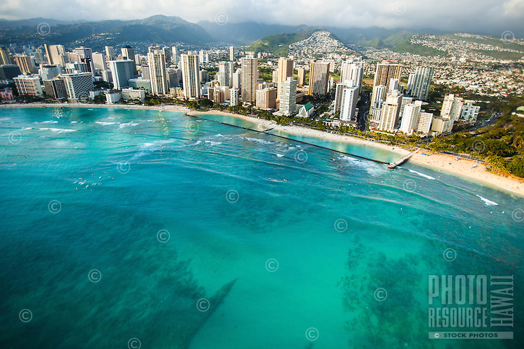 An aerial view of the Waikiki Strip right before sunset, with surfers waiting for waves to the left, O'ahu.