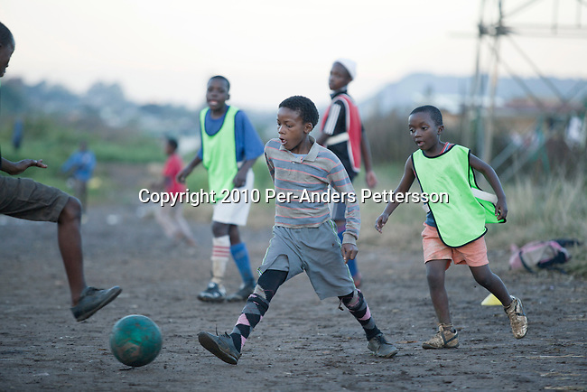 SOWETO, SOUTH AFRICA - MAY 7: Young boys play a street soccer game on May 7, 2010, in the Motswaldi section in Soweto, Johannesburg, South Africa. Thousands of young boys play soccer in townships such as Soweto, dreaming about being the next big star. The upcoming World Cup soccer tournament in the country has greatly increased the soccer interest in the country. Many of these teams and players are very poor and can't afford proper clothes and shoes. (Photo by Per-Anders Pettersson)