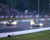 Jun 5, 2015; Englishtown, NJ, USA; NHRA funny car driver Cruz Pedregon (right) races alongside Tim Wilkerson during qualifying for the Summernationals at Old Bridge Township Raceway Park. Mandatory Credit: Mark J. Rebilas-
