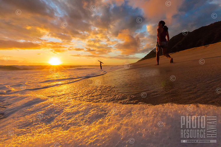 Beachgoers enjoy the beautiful sunset at Yokohama Bay on the West Coast of O'ahu.