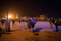 A camel stands waiting for tourist pictures in the plaza outside the Id Kah Mosque in central Kashgar, Xinjiang, China.  The mosque is the spiritual center of Uighur culture, and in recent years, stones in the plaza outside the mosque indicating the direction of Mecca have been removed.