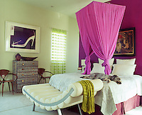 A dog dozes beneath the pink mosquito net that hangs above the bed in the master bedroom