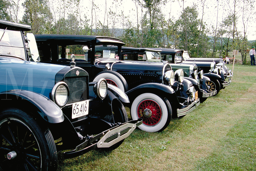A row of 1920's and 1930's cars at a classic-antique auto meet. A 1922 Studebaker is at left foreground. nostalgia, automobiles, vintage, classic. Vermont.