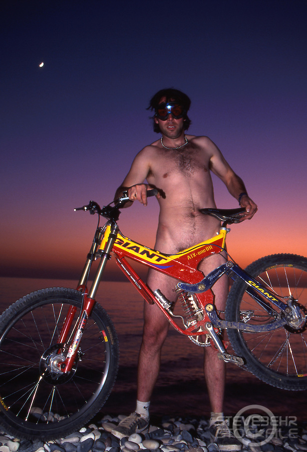 Rob Warner naked at sunset with Giant DH bike .Cyprus , 1998.pic copyright Steve Behr / Stockfile