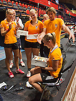 The Netherlands, Den Bosch, 16.04.2014. Fed Cup Netherlands-Japan, practice, Richel Hogenkamp receives a birthday cake from Arantxa Rus (L) (NED) coach Raymond Knaap, Kiki Bertens (NED) and captain Paul Haarhuis  (NED)<br /> Photo:Tennisimages/Henk Koster