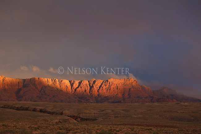 Sun spotlights the upper rock ridge in the valley near Canyon Ferry in Arizona during a late day thunderstorm